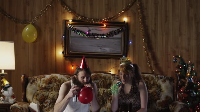ms td couple having party in living room at christmas / orem, utah, usa - party hat video stock e b–roll