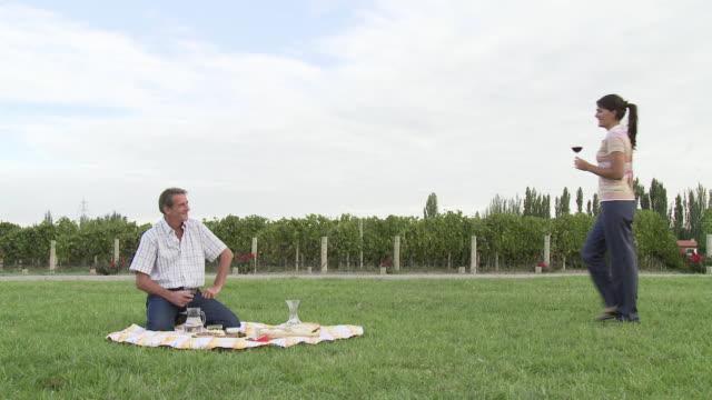 Couple having picnic in vineyard
