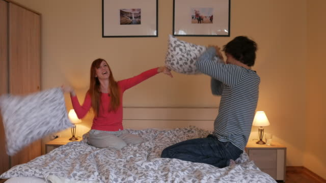 vídeos y material grabado en eventos de stock de par tener lucha con almohada en la cama - lucha con almohada
