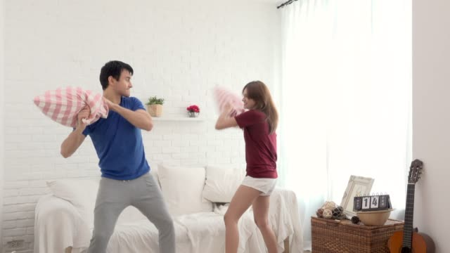 Couple Having Pillow Fight In Living Room