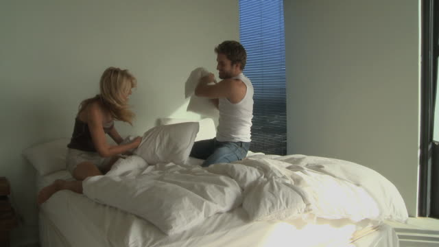 vidéos et rushes de ws couple having pillow fight on bed / cape town south africa - oreiller