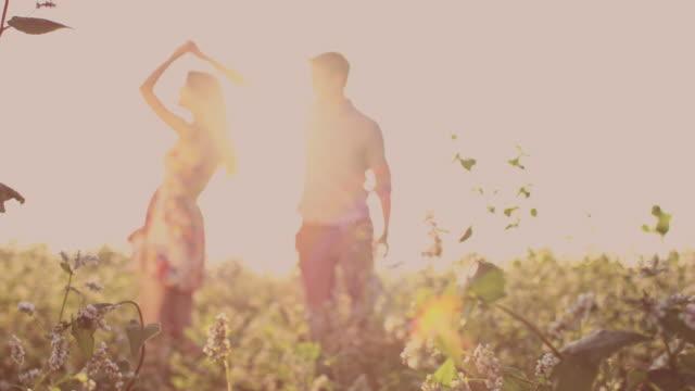 SLO MO Couple having romantic moments in buckwheat field