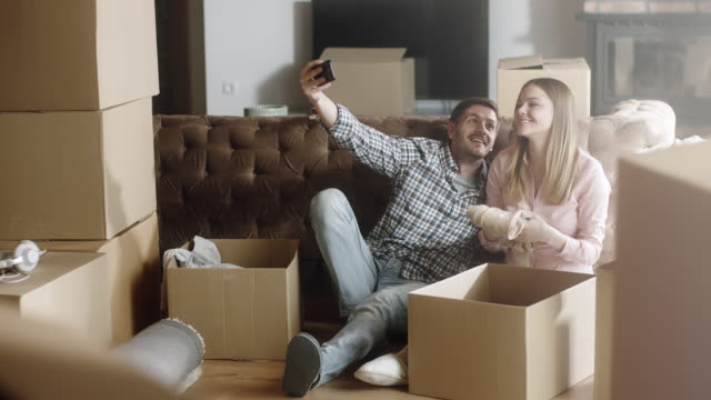 Couple having selfies at home while unpacking