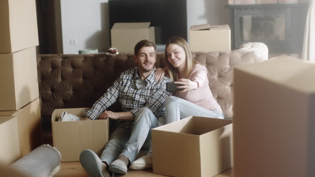 couple having selfies at home while unpacking - move stock videos and b-roll footage