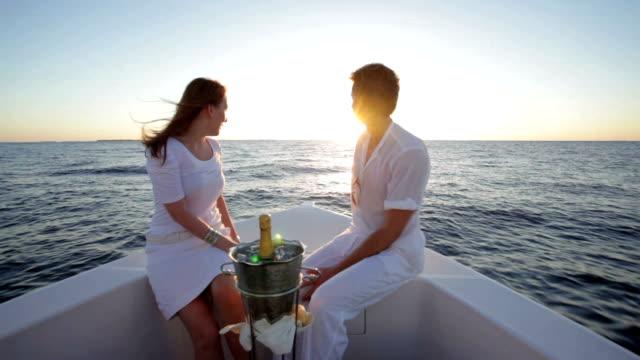 vidéos et rushes de couple heading into sunset on a boat - cadrage aux genoux