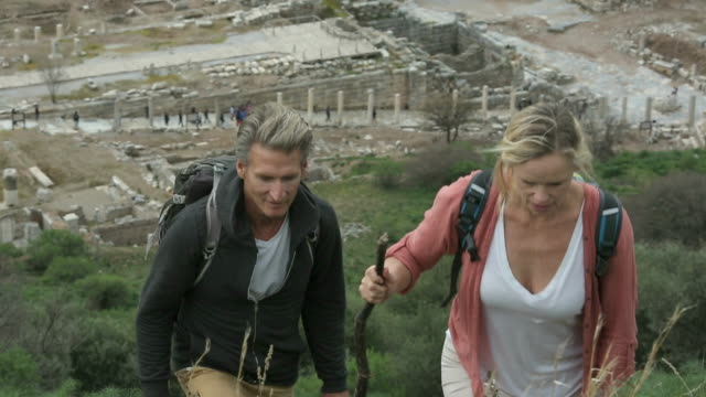 Couple hike above ruins of ancient Greek civilization