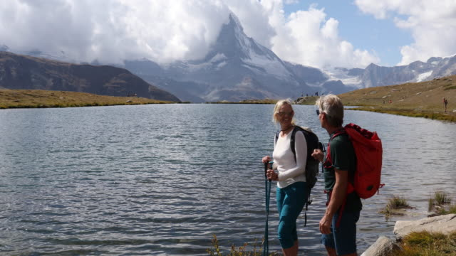 couple hike along lake edge, matterhorn distant - mature couple stock videos & royalty-free footage