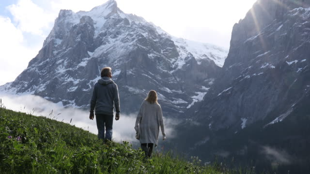 couple hike through meadow below snowy mountains - 55 59 jahre stock-videos und b-roll-filmmaterial