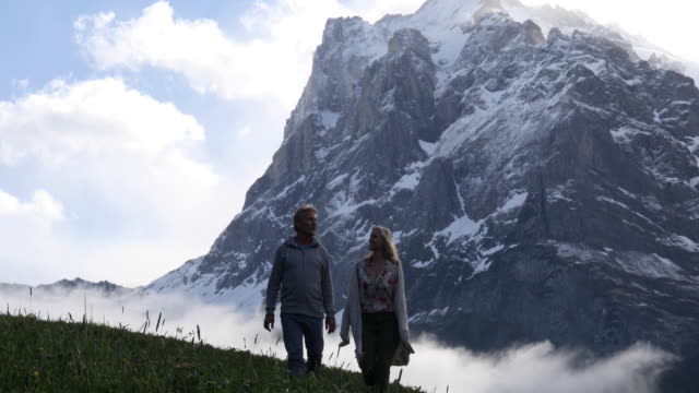 vídeos de stock e filmes b-roll de couple hike through meadow below snowy mountains - adulto maduro