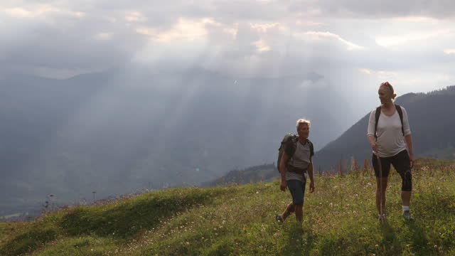 couple hike up through mountain meadow at sunrise - climbing equipment stock videos & royalty-free footage