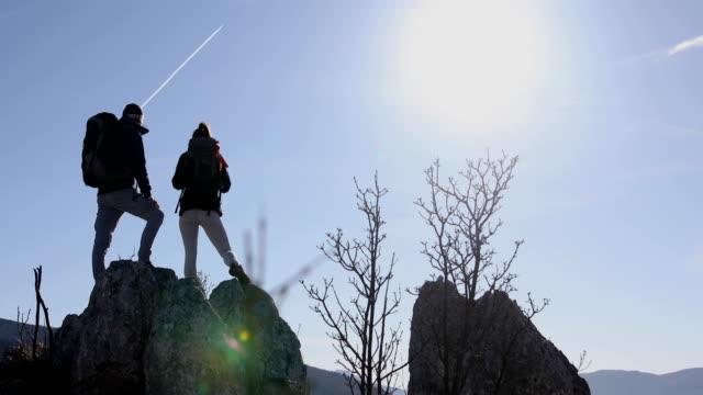 vídeos de stock e filmes b-roll de couple hikers on rocky mountain range looking at beautiful inspirational landscape view - andar depressa