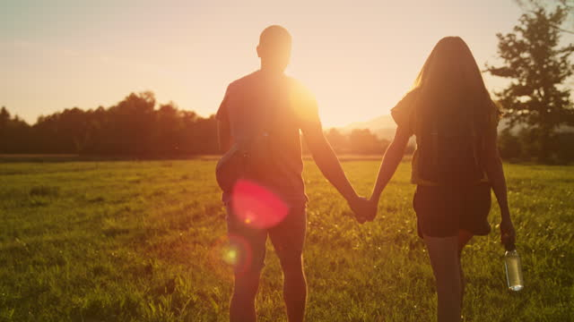 slo mo ts a couple hiking across a field at sunset and holding hands - outdoor pursuit stock videos & royalty-free footage