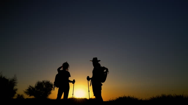 couple hiking during sunset over horizon - clear sky stock videos & royalty-free footage