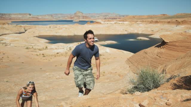 vídeos de stock e filmes b-roll de couple hiking in the desert - lago powell