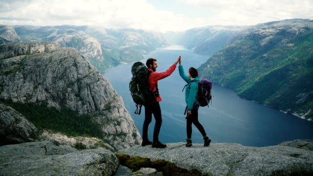 vídeos de stock e filmes b-roll de couple  hiking near preikstolen and giving high five at lysefjorden - estrada da vida