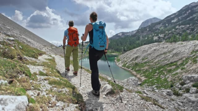 Couple hiking on a narrow gravel path above a mountain lake in sunshine