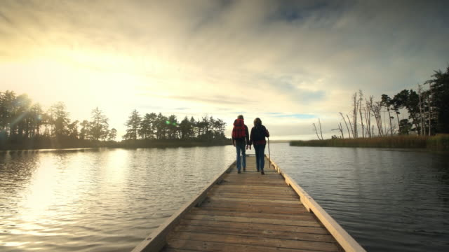 couple hiking on dock on lake at sunset - ganzkörperansicht stock-videos und b-roll-filmmaterial
