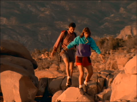 vídeos de stock, filmes e b-roll de couple hiking over rocks toward tent / man with backpack - 2001