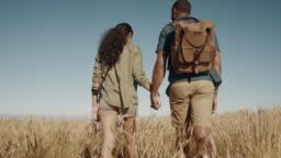 Couple hiking through dry grass on a mountain