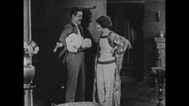 1925 Couple hold foundling baby awkwardly before taking it to bedroom