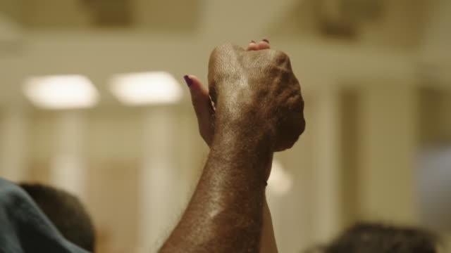 vídeos de stock, filmes e b-roll de couple hold hands into air during mass at church - igreja