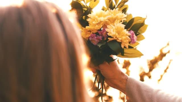 stockvideo's en b-roll-footage met paar boeket bloemen bij elkaar te houden - cadeau