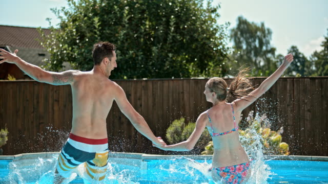 slo mo td couple holding hands and jumping into the pool - arms outstretched stock videos & royalty-free footage
