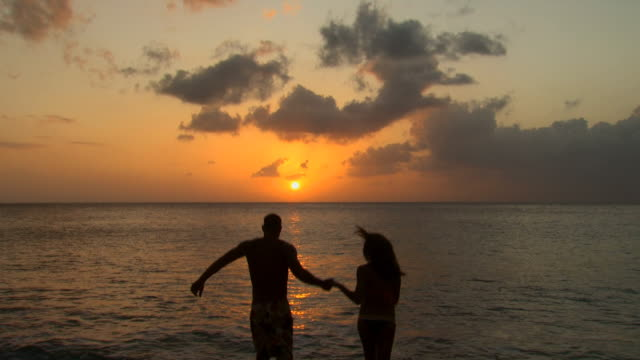 couple holding hands and swimming at sunrise or sunset - see other clips from this shoot 1142 stock videos & royalty-free footage