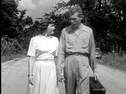 ms, b/w, couple holding hands and talking while walking on rural road, usa - anno 1950 video stock e b–roll