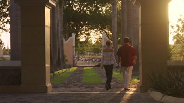 vídeos y material grabado en eventos de stock de ms couple holding hands and walking between columns at hacienda xcanatun / merida, mexico  - mérida méxico