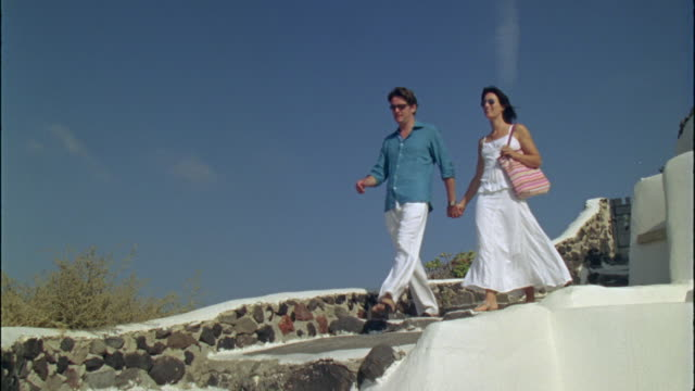 LA WS Couple holding hands and walking down stone steps / Santorini, Greece