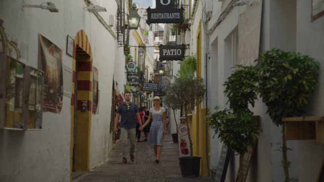 couple holding hands and walking on narrow urban sidewalk / cordoba, cordoba, spain - narrow stock videos & royalty-free footage