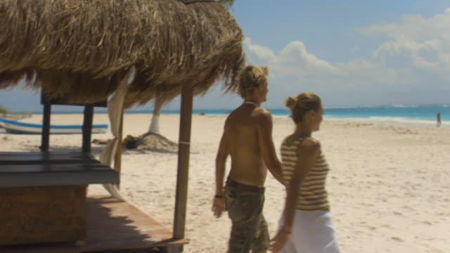 sm ms pan couple holding hands and walking past massage hut on beach/ tulum, mexico - massagetisch stock-videos und b-roll-filmmaterial