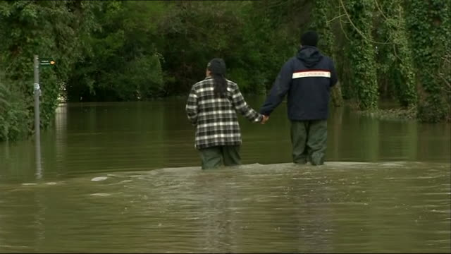 couple holding hands and walking through kneehigh floodwater in the thames valley after thames river breaks it's banks - knee highs stock videos and b-roll footage