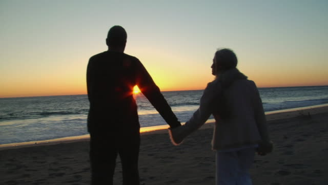WS Couple holding hands and walking toward beach at sunset/ Sycamore Cove, California
