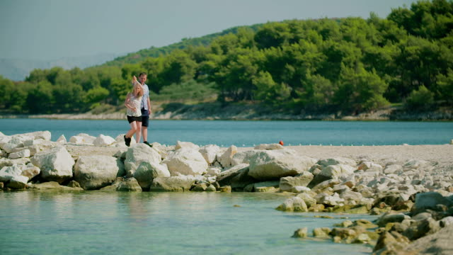 Couple Holding Hands and Walks on Shore
