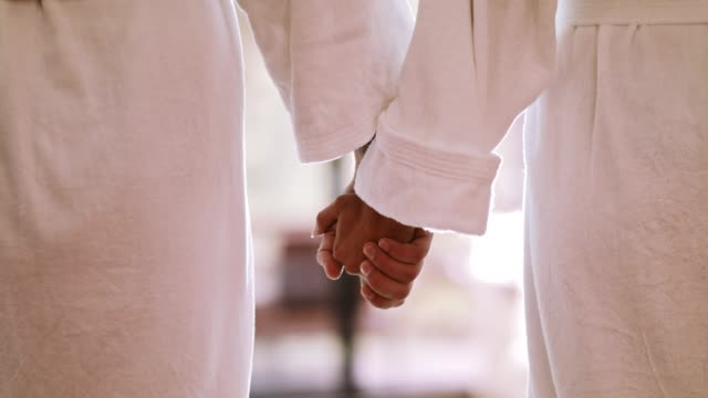 couple holding hands at spa, midsection - bathrobe stock videos & royalty-free footage