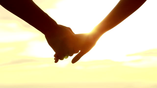 couple holding hands at sunset , slow motion - back lit stock videos & royalty-free footage