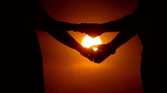 CLOSE UP Couple holding hands at sunset