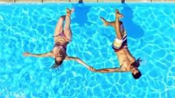 SLO MO CS Couple holding hands falling into pool backwards