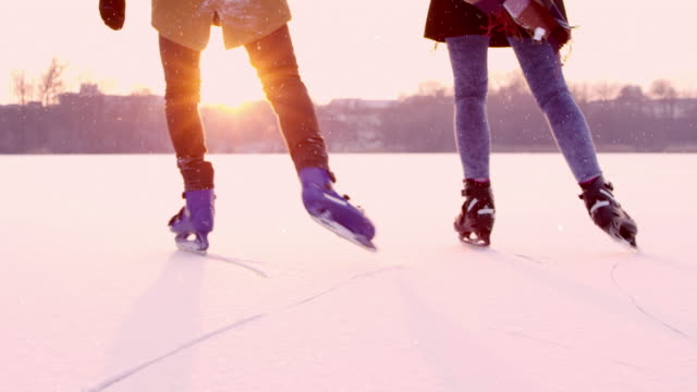 4k couple holding hands ice skating on sunny frozen lake, real time - winter sport stock videos and b-roll footage