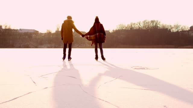 4k couple holding hands ice skating on sunny frozen lake, slow motion - ice skating stock videos & royalty-free footage
