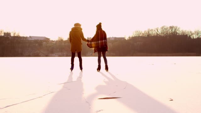 4K Couple holding hands ice skating on sunny frozen lake, slow motion