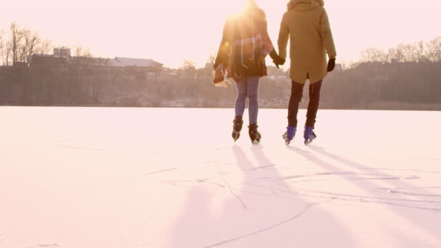 4k couple holding hands ice skating on sunny frozen lake, slow motion - winter sport stock videos & royalty-free footage