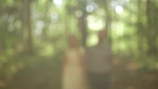 Meio tiro Plano Charriot Desfocar o plano aproximado Casal segurando as mãos em floresta em dia de sol
