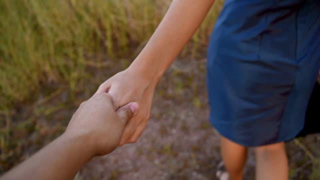 vídeos y material grabado en eventos de stock de pareja manteniendo las manos en campo de hierba - agarrados de la mano
