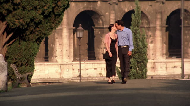 couple holding hands + kissing walking toward camera with colosseum in background / rome, italy - boyfriend video stock e b–roll