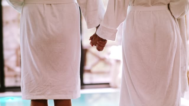 Couple holding hands next to the pool