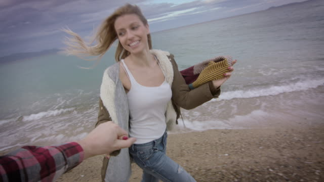 vídeos de stock, filmes e b-roll de de mãos dadas de casal na praia 4k - overcast