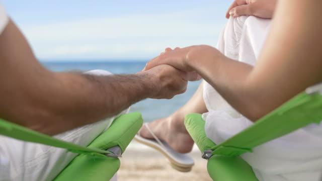 vídeos de stock, filmes e b-roll de hd: casal de mãos dadas na praia - cadeira dobrável